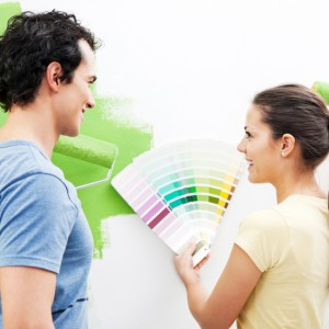 Portrait of a couple holding color swatch and choosing the color for the wall.